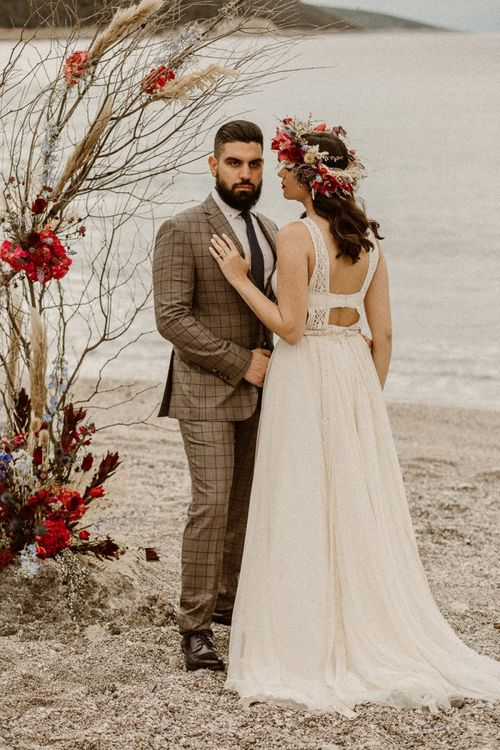 Bride in backless wedding dress with flower crown and groom in checked suit