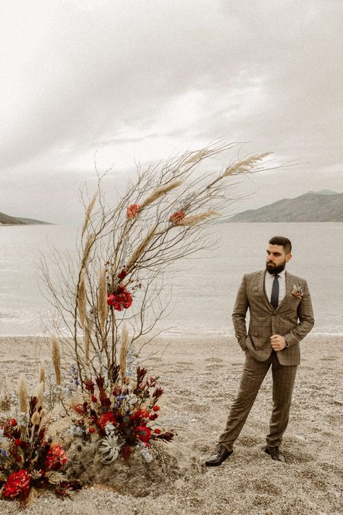Groom in beige and blue checked suit standing at the beach