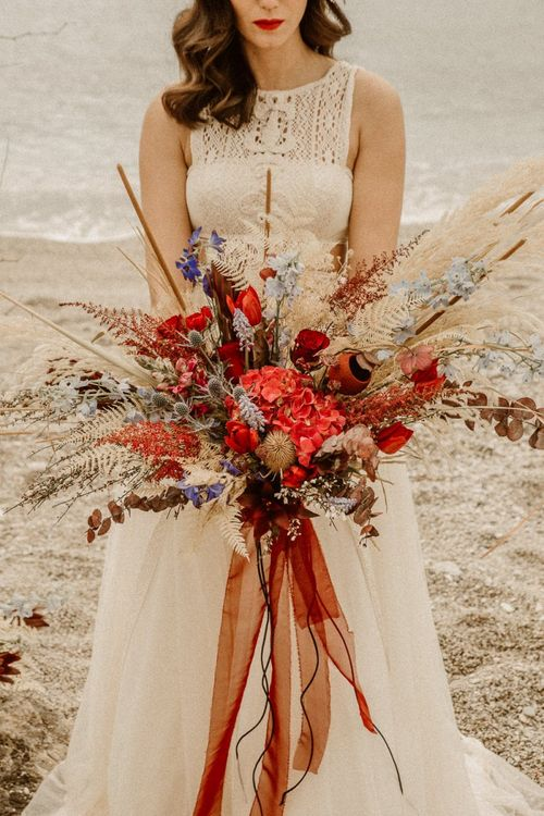 Oversized bridal bouquet with red flowers and dried grasses