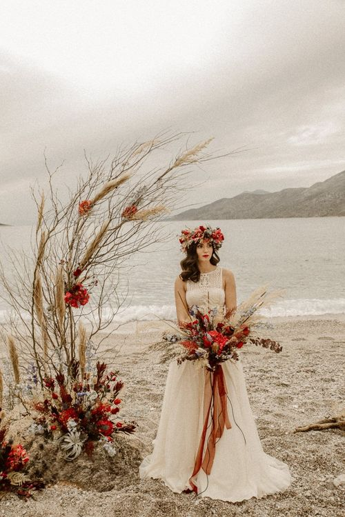 boho bride in lace wedding dress with red flower crown and bridal bouquet for beach elopement