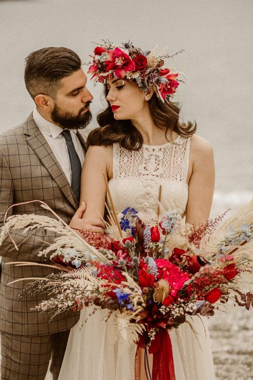 Boho bride in lace wedding dress with red flower crown and bridal bouquet