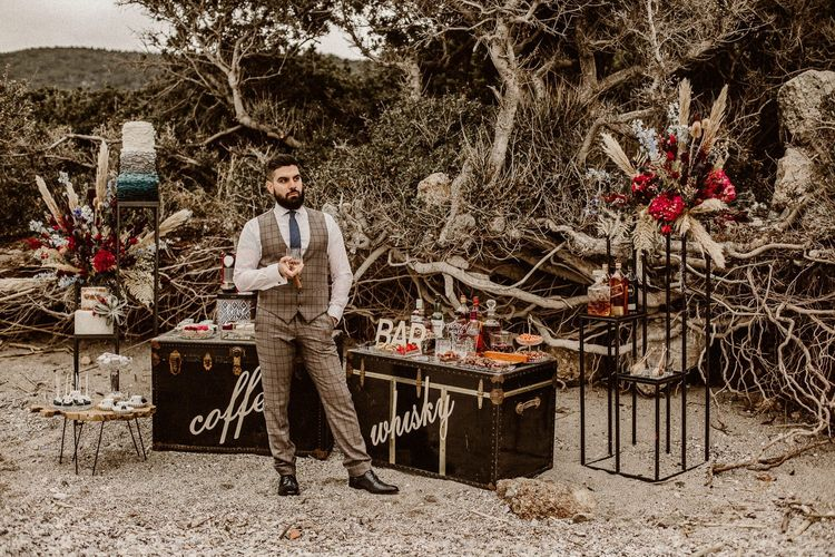 Groom at coffee and whiskey stations on the beach