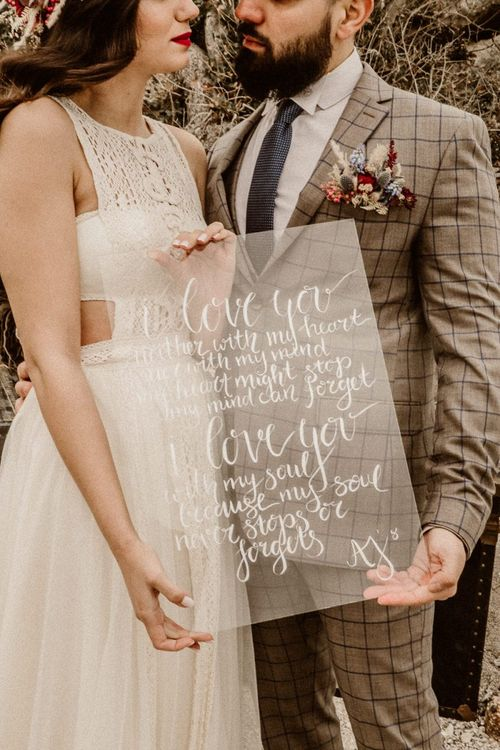 Bride and groom holding perspex wedding sign