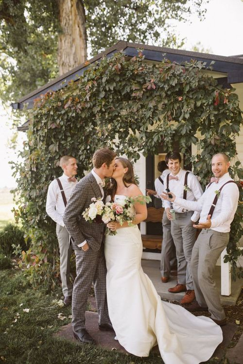Bride in Fishtail Wedding Dress and Groom in Brown Check Suit Kissing
