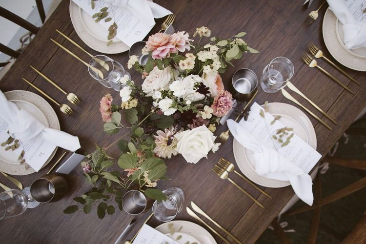 Elegant Table Place Settings with Gold Cutlery and Floral Centrepiece