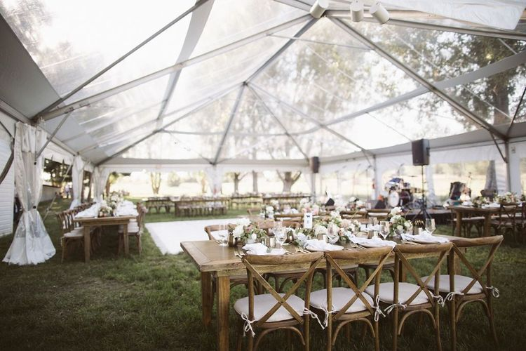 Outdoor Glasshouse Marquee Reception with Wooden Tables and Floral Centrepieces