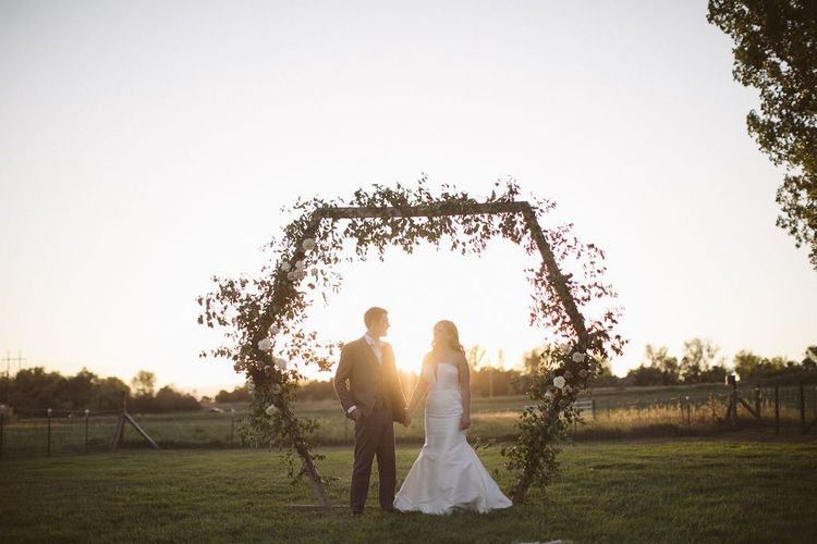 Bride and Groom Standing in Front of a Hexagonal Arch During Sunset