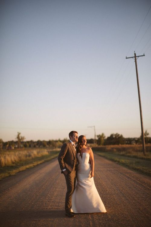 Golden Hour Portrait with Bride in Fishtail Wedding Dress and Groom in Brown Check Suit