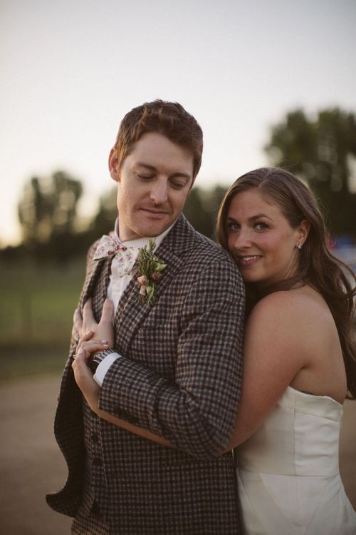 Bride in Off the Shoulder Wedding Dress Embracing Her Groom in a Brown Check Suit