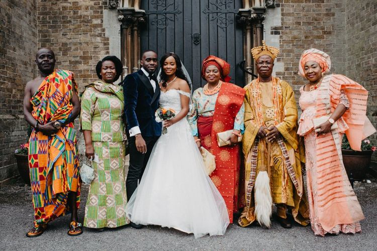 Bride and groom with wedding guests in traditional African wedding attire