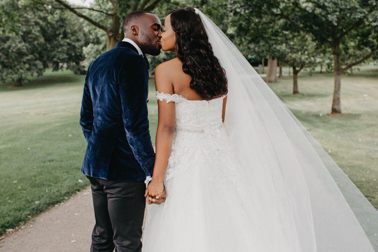Bride and groom kissing in off the shoulder wedding dress and velvet jacket