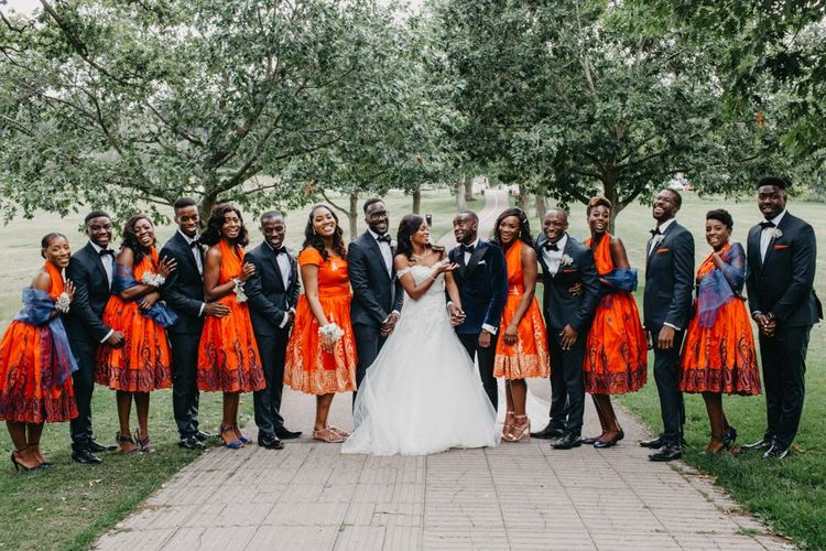 Wedding party portrait with groomsmen in navy suits and bridesmaids in orange dresses for African wedding