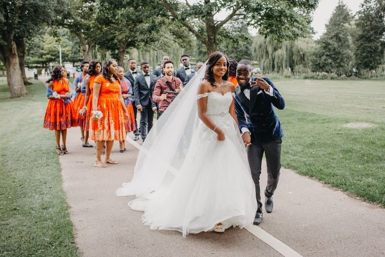 Bride and groom walking along with their wedding party at African wedding