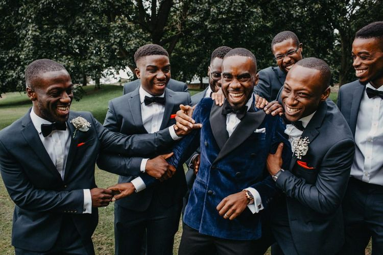 Groom in velvet jack and groomsmen in navy suits