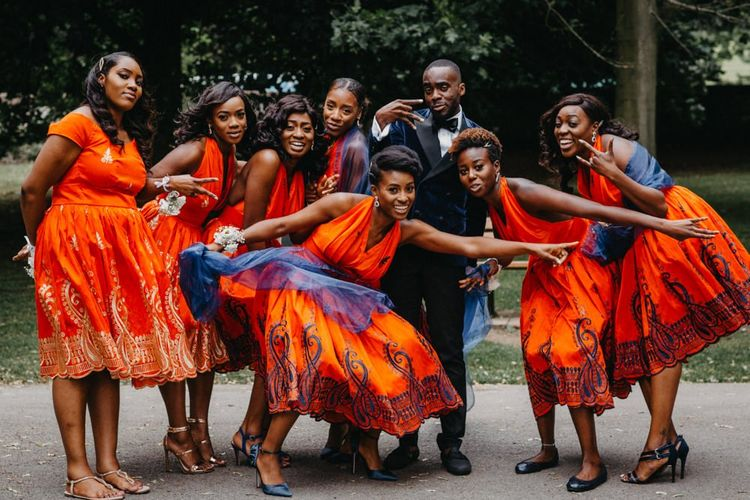 Groom in velvet blazer with the bridesmaids in bright orange dresses