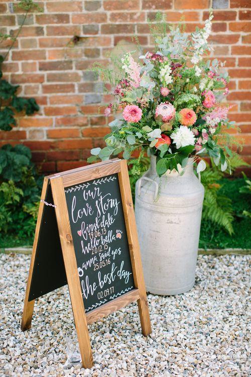 Milk Churn with Flowers and Black Board Wedding Sign | DIY Country Wedding at Warborne Farm, Lymington | Camilla Arnhold Photography