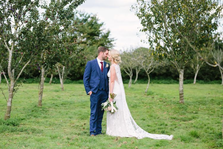 Bride in Claire Pettibone Whitney Bridal Gown with Cape | Groom in French Connection Navy Suit | DIY Country Wedding at Warborne Farm, Lymington | Camilla Arnhold Photography