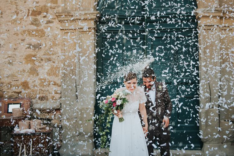 Confetti Exit | Bride in Sartoria Cucciaioni Wedding Dress | Groom in Brown Tweed Suit & Bow Tie | Stylish Pink Wedding at Terzo di Danciano, Tuscany, Italy | Lucrezia Senserini Photography | Film by Righi Photography
