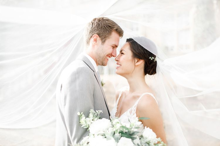 Beautiful Couple Under Wedding Veil With White Flowers