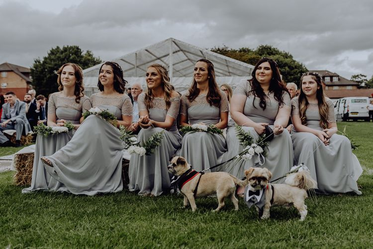 Bridesmaids in Grey ASOS Dresses Sitting on Hay Bales at the Outdoor Wedding Blessing