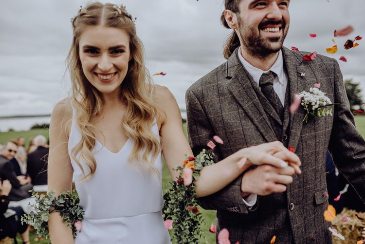Confetti Moment with Bride in Slip Wedding Dress and Groom in Brown Check Suit