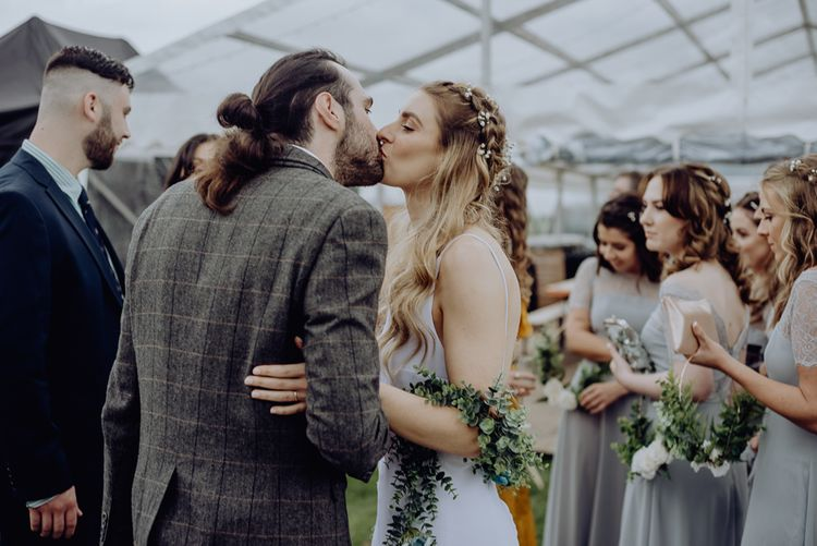 Boho Bride with Half Up Half Down Hair Kissing Groom with Top Knot