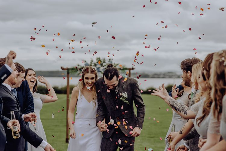 Colourful Confetti Moment with Bride in Slip Wedding Dress and Groom in Brown Check Suit