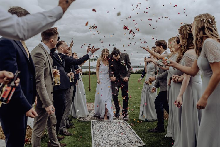 Bright Confetti Moment with Bride in Spaghetti Strap Wedding Dress and Groom in Wool Suit
