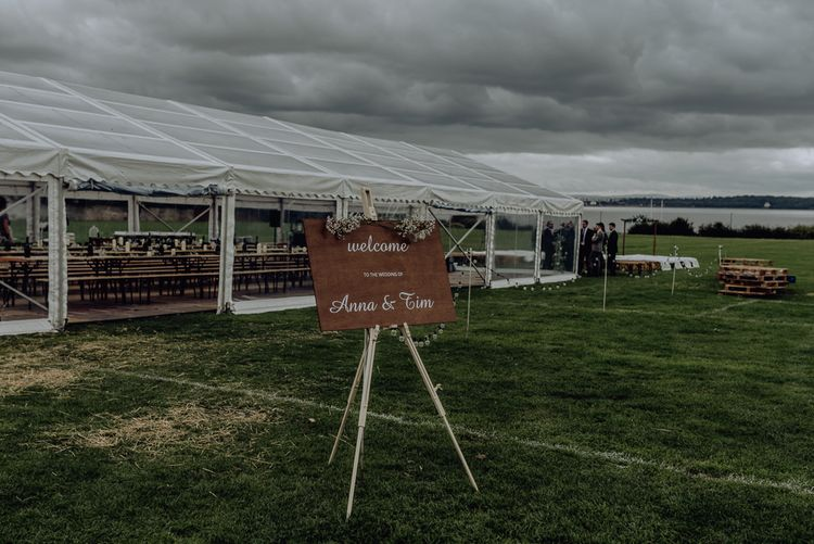Wedding Welcome Sign on an Easel Outside Clear Sided Marquee Reception