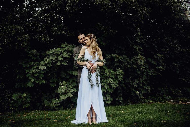 Boho Bride in Spaghetti Strap Wedding Dress and Ivy Garland with Groom in Brown Check Suit