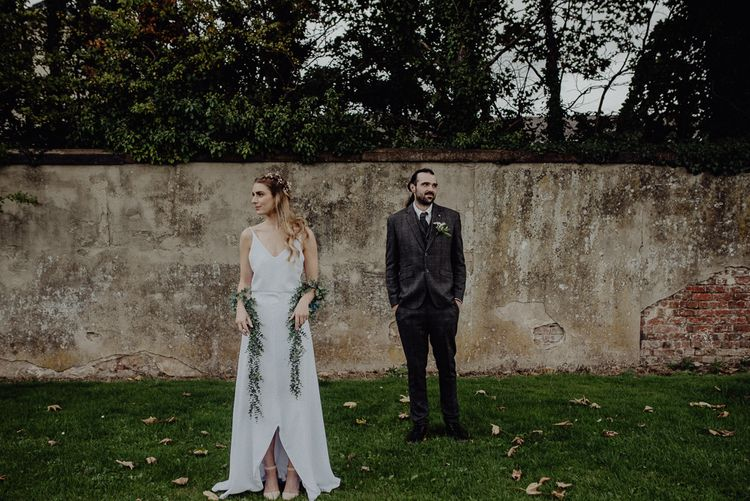 Boho Bride in Slip Wedding Dress and Ivy Garland with Groom in Brown Check Suit
