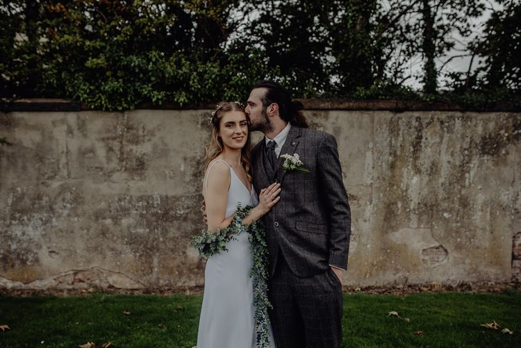 Boho Bride in High Low Slip Wedding Dress and Ivy Garland with Groom in Brown Check Suit Embracing