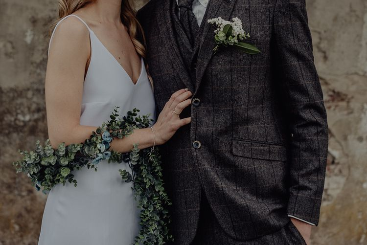 Boho Bride in Slip Wedding Dress and Ivy Garland with Groom in Three-piece Wool Suit Embracing