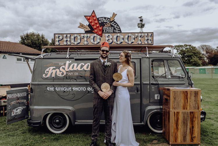 Bride and Groom Standing in Front of Photo Booth Van
