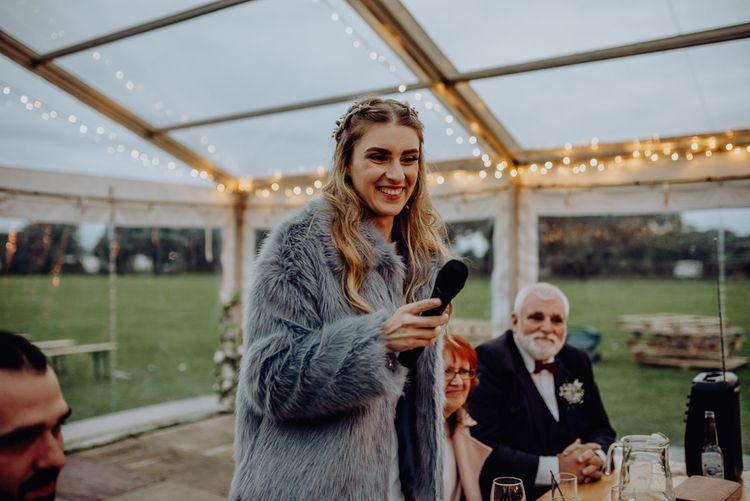 Bride in Grey Faux Fur Coat Giving Her Wedding Speech