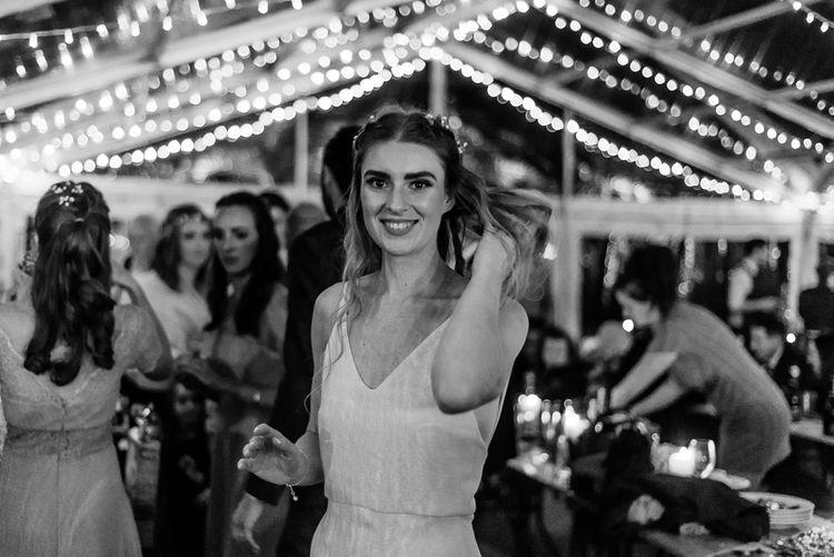 Bride in Wedding Dress with Straps Enjoying Fairy lit Reception