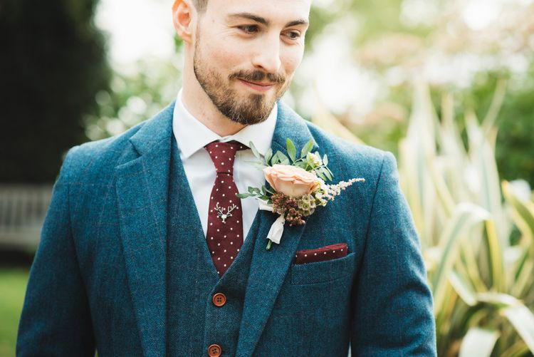 Groom Navy Tweed Suit with Burgundy Tie and Floral Button Hole
