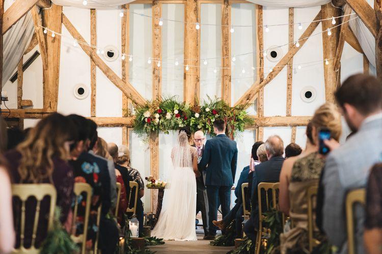 Bride and Groom During Wedding Ceremony in Barn Venue