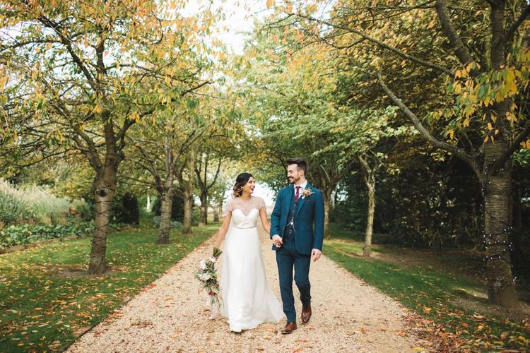 Bride and Groom After Ceremony in Beaded Bride Dress and Navy Tweed Suit