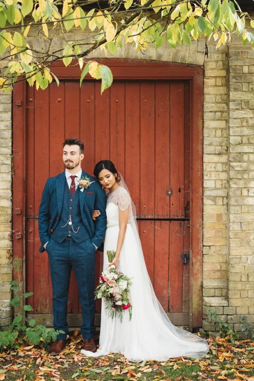Groom Wearing Tweed Navy Suit with Bride Holding Autumnal Bouquet