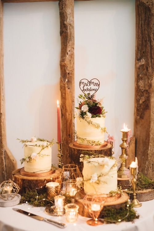 Beautiful Rustic Cake Table with Candles and Foliage with Cakes on Tree Slices