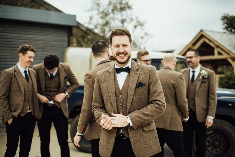 Groom in tweed suit with bowtie for Oxfordshire barn wedding