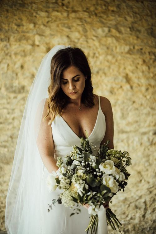 Bride in minimalist Sassi Holford wedding dress with bouquet
