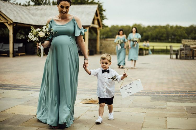 Pregnant bridesmaid with cute pageboy carrying wedding sign