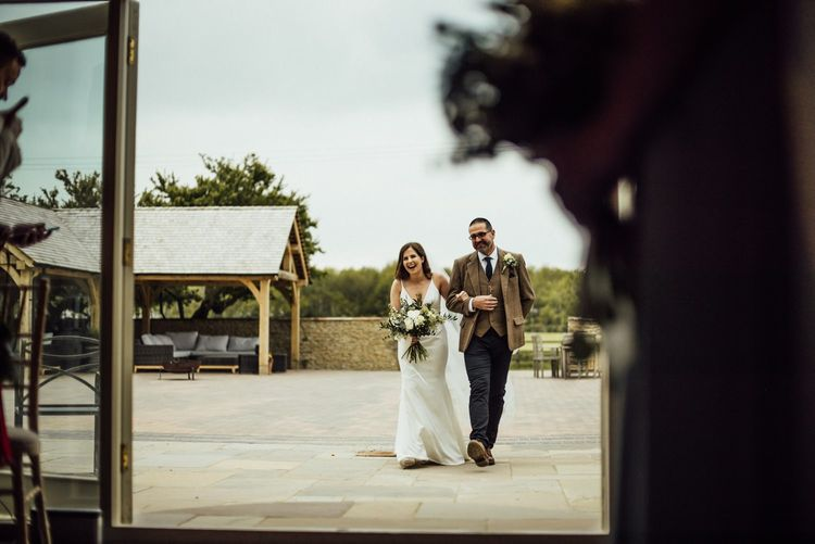 Bride makes entrance at Oxfordshire barn wedding ceremony with father