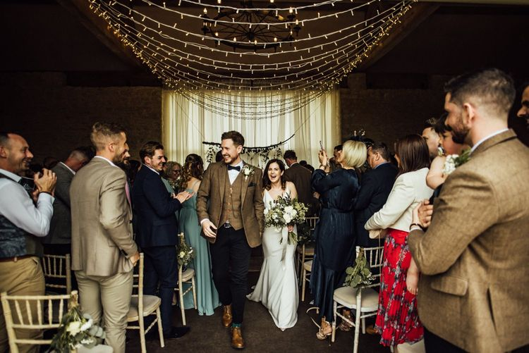 Bride and groom walk back down aisle as husband and wife under fairy light canopy