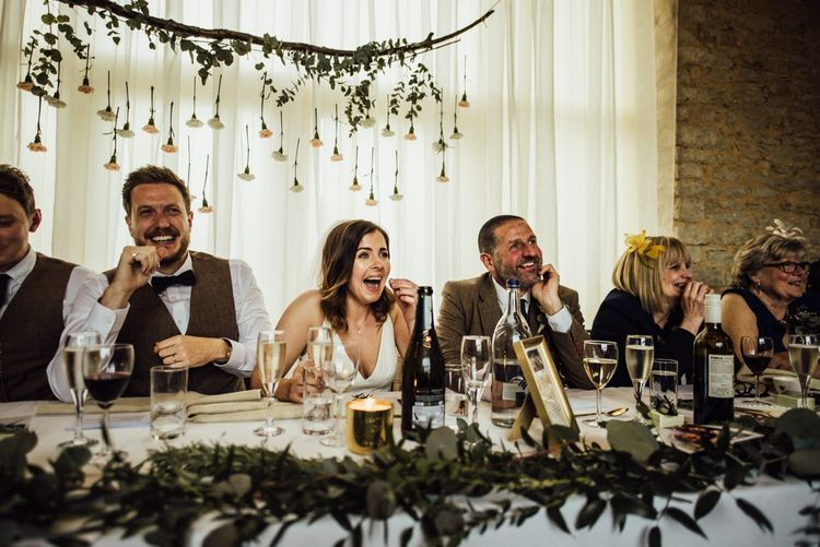 Bride and groom enjoys wedding speeches with flowers hanging behind them