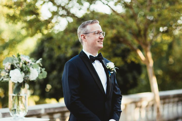 Groom standing at the altar in a tuxedo for destination wedding with pink bridesmaid dresses