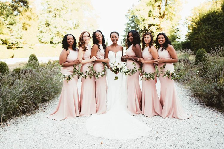 Bridal party portrait with pink bridesmaid dresses and Pronovias wedding dress