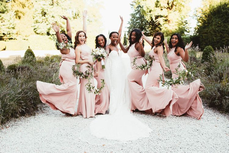Fun bridal party portrait with pink bridesmaid dresses and strapless wedding dress